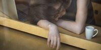 Frau liegt erschöpft neben ihrem Laptop