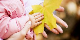 Kinder- und Erwachsenhand mit gelbemBlatt